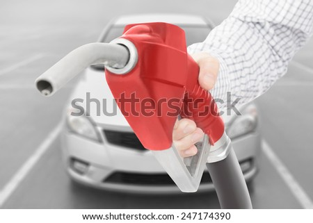 Red color fuel pump gun in hand with car on background - stock photo