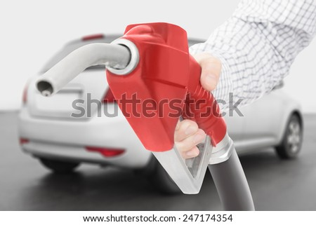 Red color fuel pump gun in hand with grey car on background - stock photo
