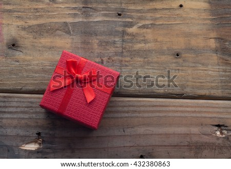 Red color gift box with bow on wooden background