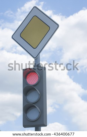 Red color on the traffic light and road sign