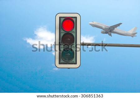 Red color on the traffic light with a beautiful blue sky in the background airliner.