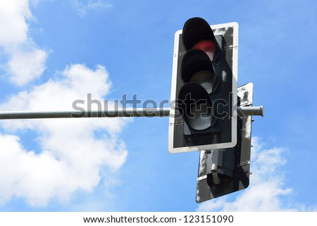 Red color on the traffic light with blue sky background