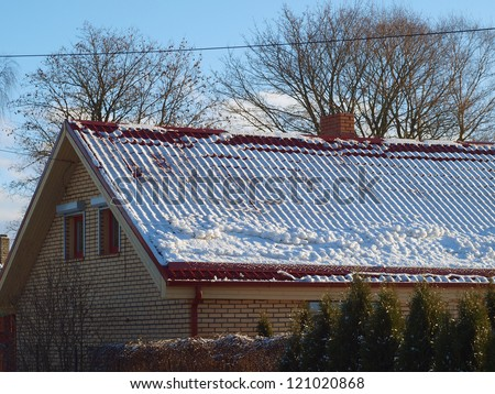 Red color snowy metal roof, with snow barrier - stock photo