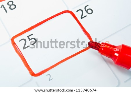 Red color writing on the calendar at 25. - stock photo