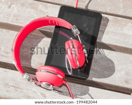 Red colored headphones and tablet PC for distance education or language course learning - stock photo