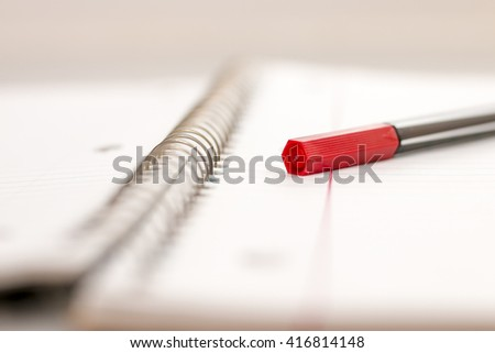 Red Colored Pen On Lined Spiral Notebook - stock photo