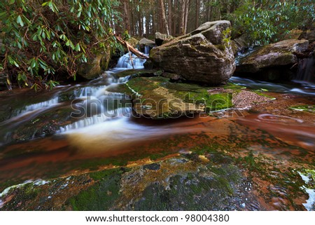 Red colored rocks, green moss and rocks in mountain stream bed - stock photo