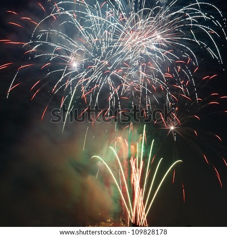 Red colorful holiday fireworks on the black sky background. - stock photo