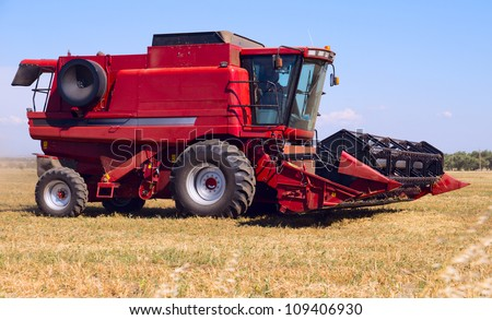 Red combine on field - stock photo