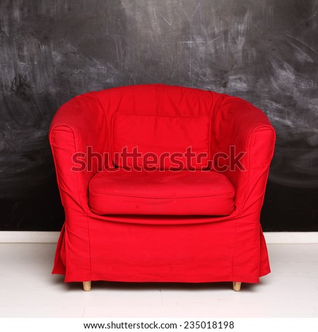 Red conceptual armchair on abstract empty blackboard background - stock photo