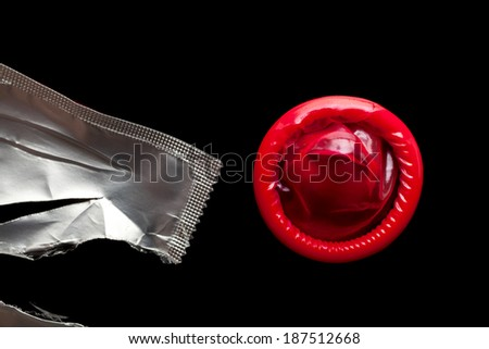 Red condom just been opened isolated on black background - stock photo