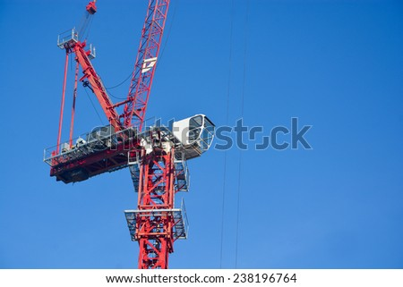 Red construction crane on clear blue sky - stock photo