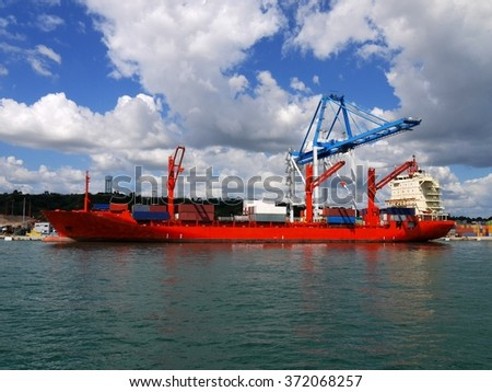 Red Container Ship alongside loading containers at container terminal.
