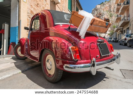 Red convertible retro car on street of Italian city - stock photo