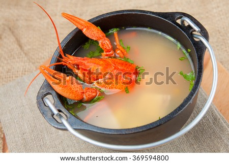 Red cooked crayfish in cauldron with soup - stock photo