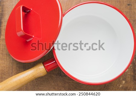 Red cooking pot vintage kitchen utensils on a wooden background. - stock photo