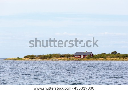 Red cottage at the beach - stock photo