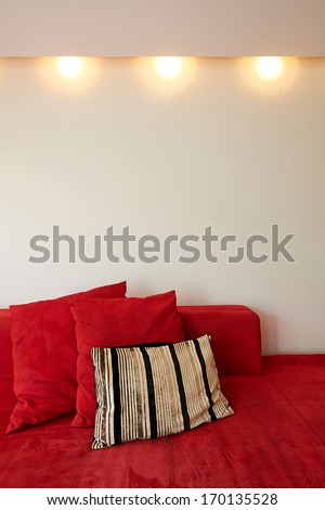 Red couch sofa and empty wall with lights