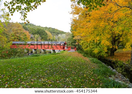 Red covered bridge over river. Autumn in old village - stock photo
