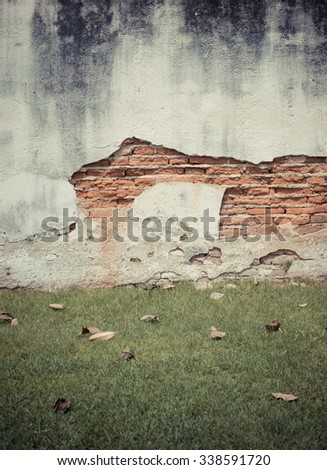 Red cracked brick wall with green grass floor
