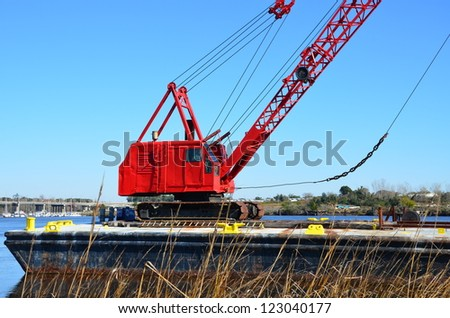 Red crane along the shore to do some heavy lifting