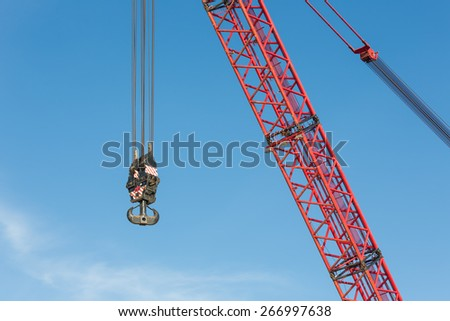 Red crane boom with steel hook against blue sky - stock photo