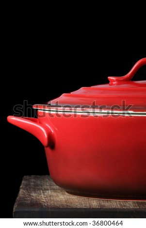 Red crock pot or casserole dish, on kitchen board, over black background. - stock photo