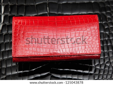 Red crocodile leather wallet laying on black leather - stock photo