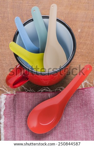 Red cup and spoon vintage kitchen utensils on a wooden background.