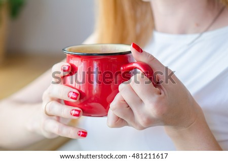 Red cup in female hand. Red manicure.