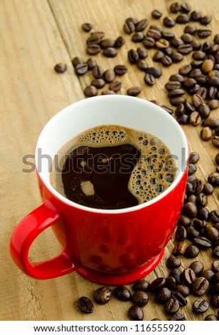 Red cup of coffee and coffee beans on rustic wooden table - stock photo