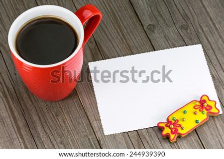 Red cup of coffee and  cookie with blank valentines greeting card on wooden table - stock photo