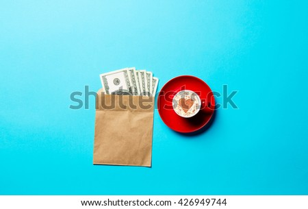 red cup of coffee and money in the envelope on the blue background - stock photo
