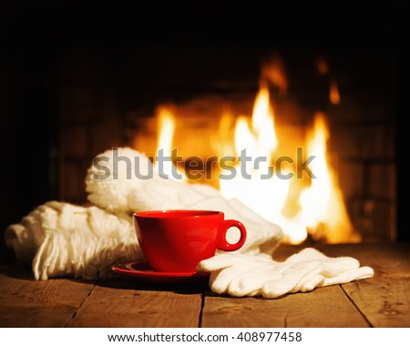 Red cup of coffee or tea, woolen scarf, gloves and cap on wooden table near  fireplace. Winter and Christmas holiday concept.