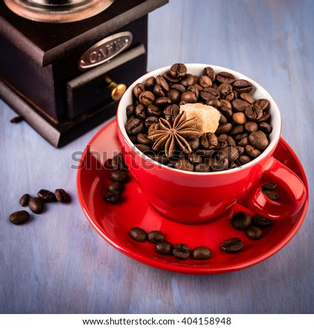 Red cup of coffee with coffee beans and mill on blue background - stock photo