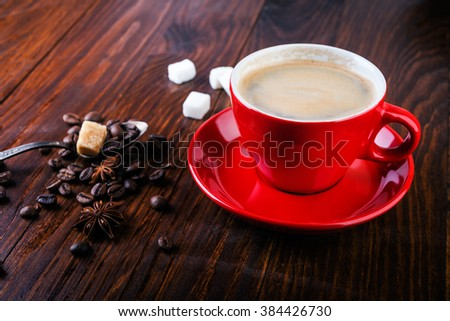 Red cup of coffee with coffee beans and sugar cubes on wooden background