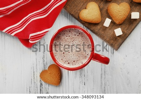 Red cup of hot cacao and heart shaped cookies on wooden background - stock photo