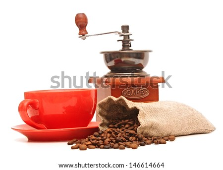 red cup with coffee beans and old coffee mill  - stock photo