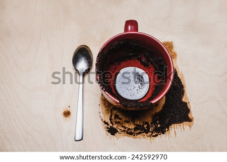 red cup with coffee on wood and coffee grounds - stock photo