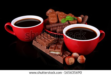 Red cups of strong coffee and chocolate bars isolated on black