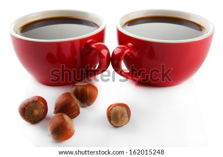 Red cups of strong coffee and nuts isolated on white