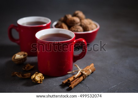 Red cups with tea on gray concrete background, cinnamon and walnuts