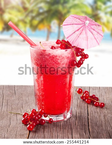 Red currant cocktail on wooden table with beach background, summer concept, fresh fruits - stock photo
