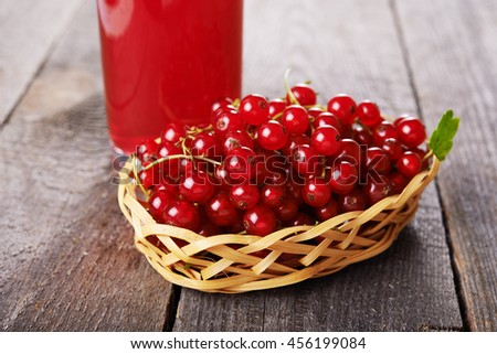 red currant in basket on wooden background - stock photo