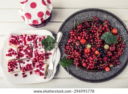 Red currant sponge cake. Plate with Assorted summer berries, raspberries, strawberries, cherries, currants, gooseberries. Fresh summer garden fruit - stock photo