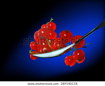 Red currants in spoon on a blue background - stock photo