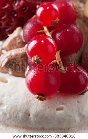Red currants on meringue cake; close-up - stock photo