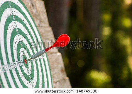 Red dart hits bull's eye of the dartboard - stock photo