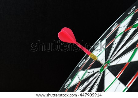 Red dart hitting on target with black background