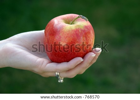 Red Delicious apple in a young woman's hand